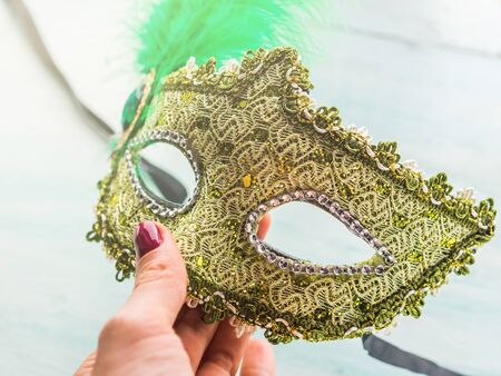 Carnival Mardi gras golden mask in womans hand.