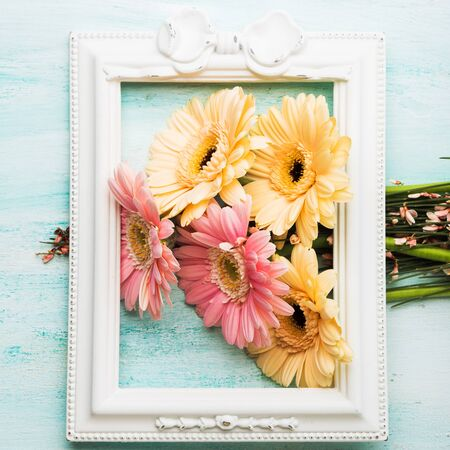 Beautiful pink and yellow flowers in white frame on pastel green background. Woman, mother day greeting card.