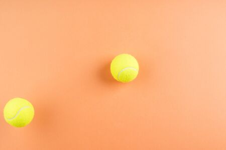 Tennis balls bouncing on orange abstract background. Competition concept 写真素材