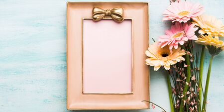 Beautiful gerbera flowers and pink frame on pastel green background. Woman, mother, Valentine day greeting card.