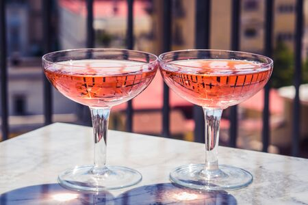 Two crystal stemmed glasses with rose wine on marble table outdoors in a cafe. Aperitif and relax time 스톡 콘텐츠 - 129594945