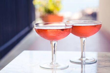 Two crystal stemmed glasses with rose wine on marble table outdoors in a cafe. Aperitif and relax time 스톡 콘텐츠 - 129594857