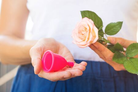 Woman holding a pink menstrual cup in hands. Closeup Stock Photo