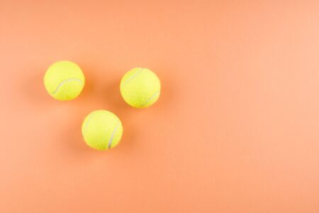 Three Tennis balls on orange abstract background. Competition concept 스톡 콘텐츠 - 129594844