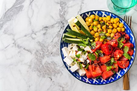 Colorful turmeric chickpea watermelon salad with feta cheese, tomatoes, zucchini, mint and balsamic vinegar on marble table. Summer fresh easy lunch. Flat lay 스톡 콘텐츠 - 130014198
