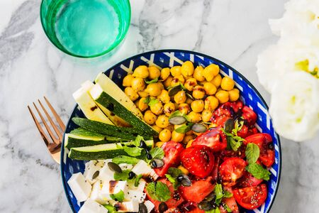 Colorful turmeric chickpea watermelon salad with feta cheese, tomatoes, zucchini, mint and balsamic vinegar on marble table. Summer fresh easy lunch 스톡 콘텐츠 - 130014202