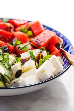 Colorful turmeric chickpea watermelon salad with feta cheese, tomatoes, zucchini, mint and balsamic vinegar on marble table. Summer fresh easy lunch 스톡 콘텐츠