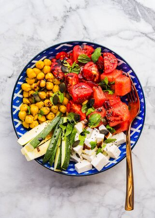 Colorful turmeric chickpea watermelon salad with feta cheese, tomatoes, zucchini, mint and balsamic vinegar on marble table. Summer fresh easy lunch. Flat lay 스톡 콘텐츠 - 130014207