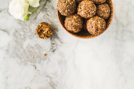 Energy protein balls with healthy ingredients on marble table. Home made with dates, peanut butter, flax and chia seeds, oats, almond and chocolate drops 스톡 콘텐츠 - 130014217