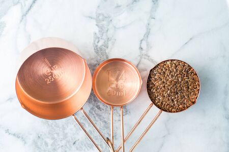 Copper measuring cups on marble table in the kitchen. Ready to cook or bulk food purchase concept. Top view 스톡 콘텐츠 - 130014222