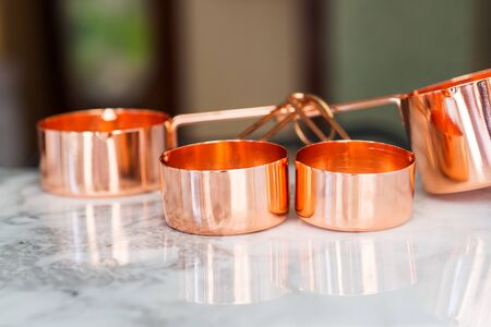 Copper measuring cups on marble table in the kitchen. Ready to cook or bulk food purchase concept 스톡 콘텐츠