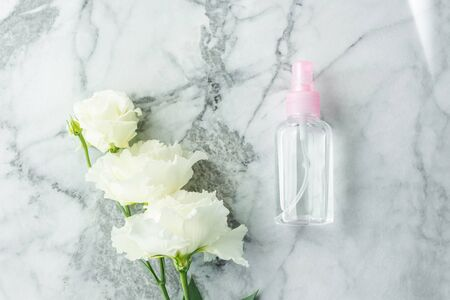 Pink transparent spray bottle and flowers on marble. Flat lay. Natural products for cleaning or body care concept 스톡 콘텐츠 - 130014237