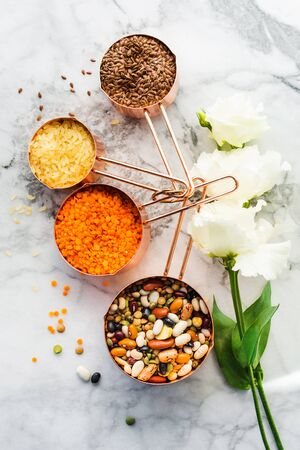Copper measuring cups on marble table with beans and cereals in the kitchen. Cooking or bulk food purchase concept. Flat lay 스톡 콘텐츠 - 130014242