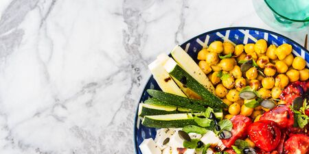 Colorful turmeric chickpea watermelon salad with feta cheese, tomatoes, zucchini, mint and balsamic vinegar on marble table. Summer fresh easy lunch. Flat lay 스톡 콘텐츠