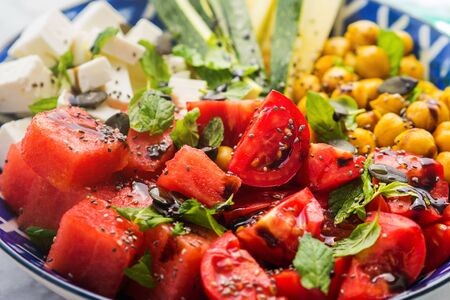 Colorful turmeric chickpea watermelon salad with feta cheese, tomatoes, zucchini, mint and balsamic vinegar on marble table. Summer fresh easy lunch 스톡 콘텐츠 - 130014252