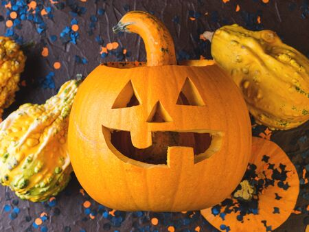 Halloween carved squash and confetti. Dark Holiday spooky background still life