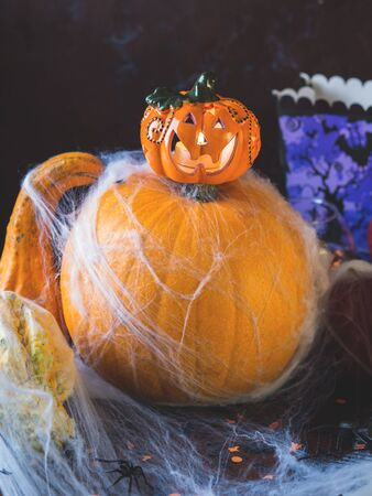 Halloween squash and candle. Spider net. Holiday spooky background still life