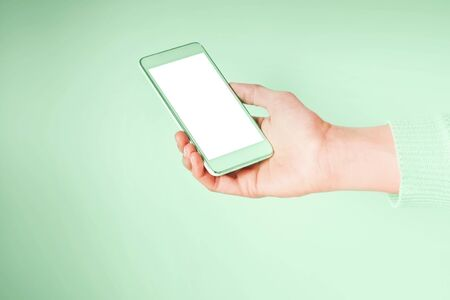 Womans hand with mobile phone screen on pastel green. Neo mint green color of 2020. 스톡 콘텐츠 - 130014429