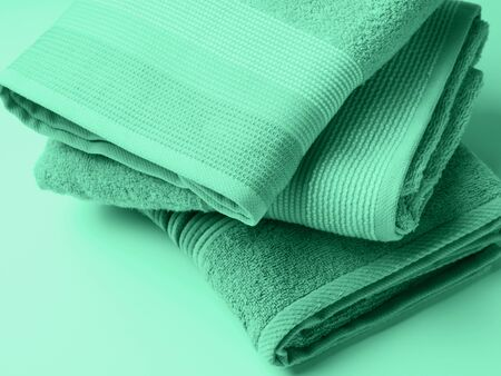Pastel color clean folded towels on monochrome background. Mint green color of 2020 스톡 콘텐츠