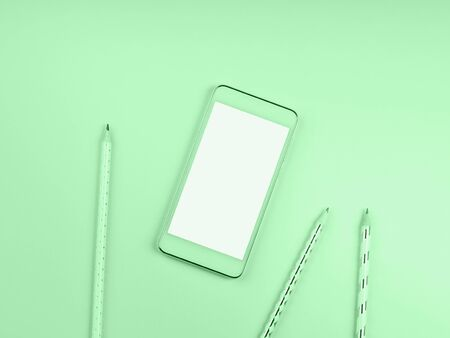 Mobile phone screen on green mint background with pencils. Minimal flat lay on color of 2020. Writing and blogging concept 스톡 콘텐츠