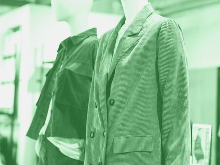 White mannequin wearing color casual jackets in a fast fashion store. Mint green color of 2020