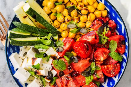 Colorful turmeric chickpea watermelon salad with feta cheese, tomatoes, zucchini, mint and balsamic vinegar on marble table. Summer fresh easy lunch. Flat lay Banque d'images