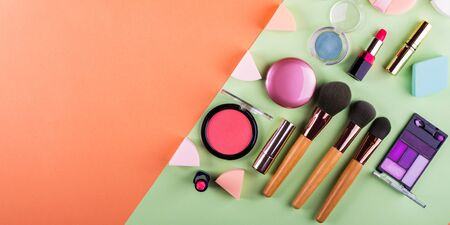 Make up accessories on orange cantaloupe and mint green background. Beauty products colorful fashion flat lay Banco de Imagens