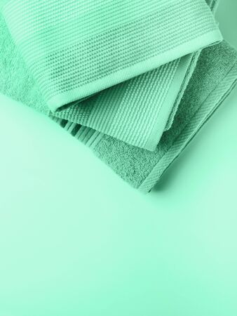 Pastel color clean folded towels on monochrome background. Mint green color of 2020 Stock Photo