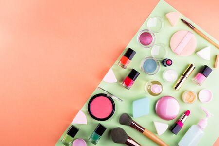 Make up accessories on orange cantaloupe and mint green background. Beauty products colorful fashion flat lay Фото со стока