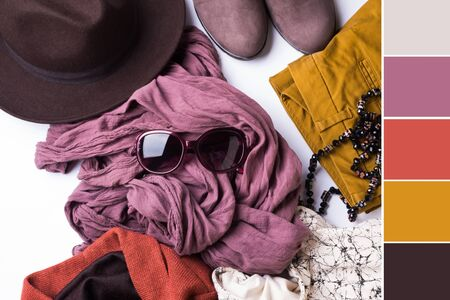 Flat lay with ladys clothes, hat, sun glasses, necklace. Autumn colours accessories on white background. Color swatch Фото со стока