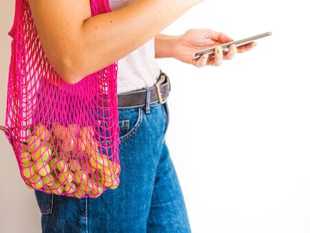 Zero waste concept. Young woman with pink reusable mesh shopping bag full of fresh grapes holding mobile phone. Plastic free lifestyle