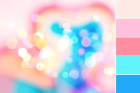 Abstract colorful blurred background with sparkling light bokeh and heart shape. Festive backdrop