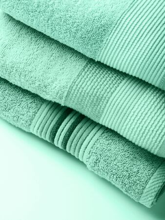 Pastel color clean folded towels on monochrome background. Mint green color of 2020 Banco de Imagens