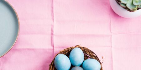 Easter festive banner for text with blue boiled eggs on pink table cloth with succulent plant. Flat lay banner Reklamní fotografie