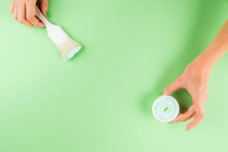 Hand with paint brush on green mint background. Redecorating, renovation concept. Fashion and interior design trend for 2020 Imagens
