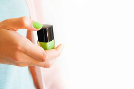 Womans hand holding green nail polish bottle of the same color of the manicure. White background copy space