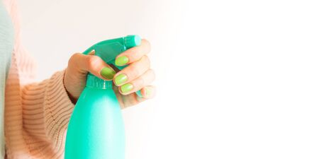 Womans hand holding mint green spray bottle with home made detergent. Natural products for cleaning or body care concept Imagens
