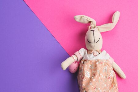 Easter bunny on bright pink and purple background. Holiday flat lay Imagens