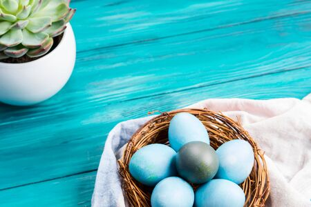Easter hard boiled blue eggs in nest on green wooden table. Traditional holiday snack. Copy space