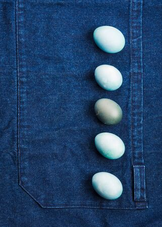Colorful blue boiled easter eggs on jeans apron background. Flat lay concept