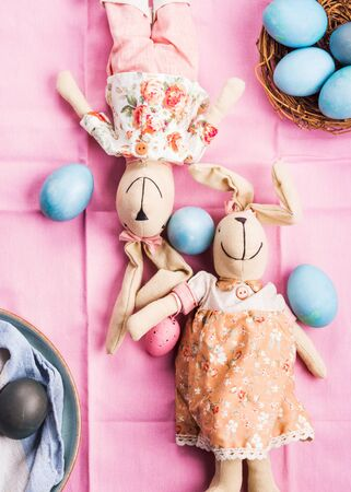 Pink easter holiday concept with bunnies and blue colored hard boiled eggs in a basket. Table decor flat lay