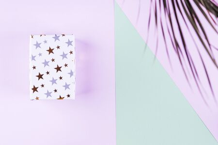 Gift box with golden stars on purple and green geometrical background. Copy space flat lay with tropical plant