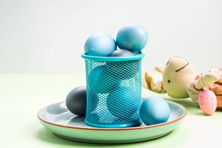 Blue easter eggs on pastel green background. Festive symbol stille life