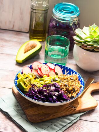 Buddha bowl with rainbow colors ingredients - avocado, fermented red cabbage, quinoa, radish, green beans, sesame and pumpkin seeds. Dish served on wooden board. Healthy vegan plant based lunch.