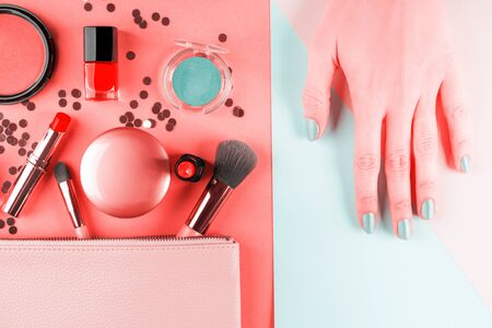 Make up products and brushes with confetti on coral pink and green background. Female hand with mint manicure