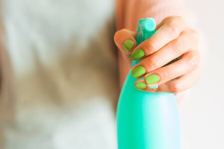 Womans hand holding mint green spray bottle with home made detergent. Natural products for cleaning or body care concept 스톡 콘텐츠