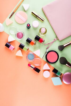 Make up accessories on orange cantaloupe and mint green background. Beauty products colorful fashion flat lay 스톡 콘텐츠