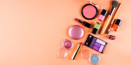 Make up accessories on orange cantaloupe background. Beauty products colorful fashion flat lay