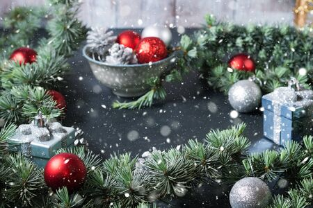 Christmas festive background on black with snow and magic light. Red and silver ornaments
