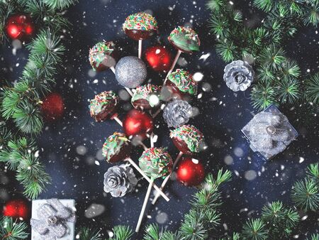 Blue spruce branches with christmas baubles and cake pops with colored sprinkles on green frosting on dark black concrete effect background. Copy space 스톡 콘텐츠